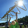 BRYAN EATON/Staff photo. Monday was a great day for physical education classes to be held outdoors as the sun was shining and the temperature was in the 70's. Kayla Conlin, 9, went along the monkey bars in Margaret Welch's class as children were doing different excercise stations while wearing pedometers.