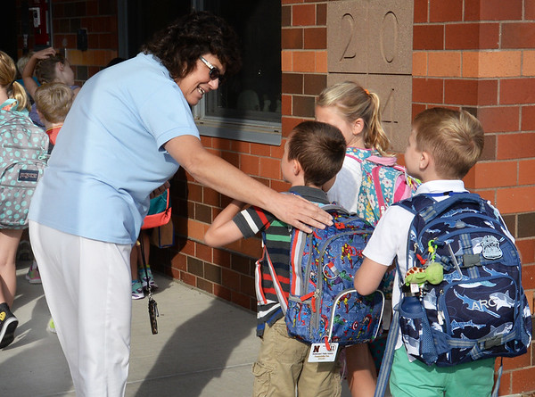BRYAN EATON/Staff Photo. Bresnahan School grade 1-3 principal Kristina Davis greets students as they head in for the first day of school yesterday.
