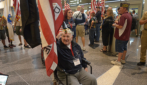 JIM VAIKNORAS/Staff photo Pearl Harbor Survivor Joseph Mielesko salutes during a send off of Honor Flight New England at Logan airport Sunday morning, over a hundred scouts, active and retire military personal, emergency response personal, civilians and a brass band were on hand to send the veterans on their way.
