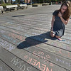 "JIM VAIKNORAS/Staff photo Christina Abouzeid of Salisburywrites with chaulk on the Newburyport Boardwalk Saturday. Someone had written ""Love Is"" and left the chaulk, obviously Christina wasn't the only one to continue the thought."