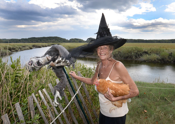 BRYAN EATON/Staff photo. Patty Ross, who calls herself the Witch of the Marsh, with her pet chicken Henrietta, is seeking the culprits who damaged the ghouls decorating her yard that she's named for relatives.