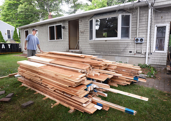 BRYAN EATON/Staff photo. Dave Giese of Piece by Piece Deconstruction and his crew removed these boards to be recycled from a single family home on 4 Moulton Street in Newburyport in July.