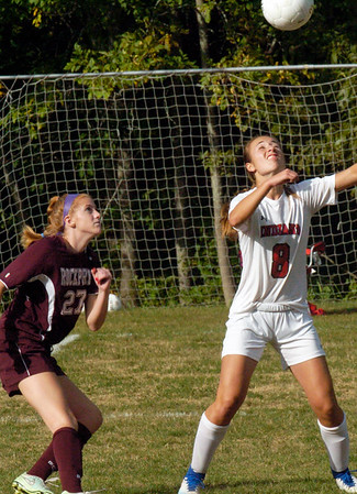 BRYAN EATON/Staff photo. Amesbury's Ashley Pettet heads the ball as Rockport's Taylor Aylward moves in.