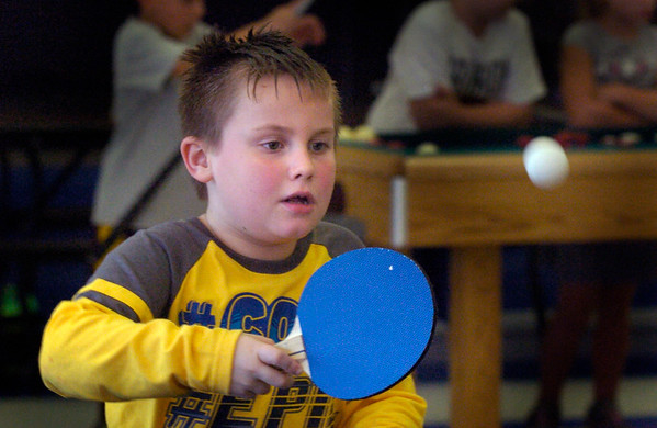 BRYAN EATON/Staff photo. Andrew Conant, 7, of Newburyport readies to return a ping pong ball to Elijah Souza, 8, of Salisbury. The two were playing the popular game at the Boys and Girls Club on Thursday afternoon.