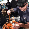 BRYAN EATON/Staff photo. South Hampton firefighter Corey Albrecht serves up chili at his department's booth at the Amesbury Fire Department's Chili Cookoff yesterday. His team says that small batch chili is the secret to good chili.