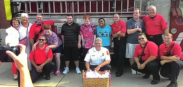 JIM SULLIVAN/Staff photo. Coastal Connections clients present gift baskets to the Amesbury Fire Department after taking a ride in the engine last Friday.