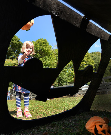 BRYAN EATON/Staff photo. Vivian Prah, 5, of Newbury throws cloth pumpkins at the Pumpkin Toss on Saturday. She was at the American Music and Harvest Festival at the Spencer-Peirce-Little Farm in Newbury.