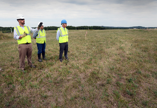 BRYAN EATON/Staff photo. Solar project project manager Sean Harrington shows Amesbury officials, including Mayor Ken Gray, right, where more solar panels will be installed over the capped landfill on South Hunt Road.
