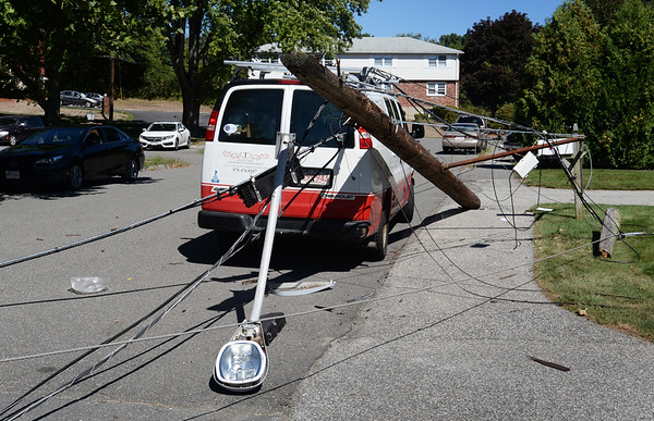 BRYAN EATON/Staff photo. This work van on Zabriskie Drive was not seriously damaged as a truck caught utility lines causing several poles to snap on nearby Low Street in Newburyport.