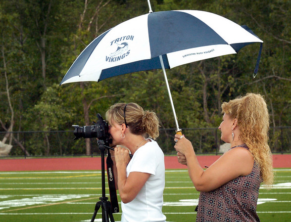 BRYAN EATON/Staff photo. Sue Landry covers photographer Kelly McHale as she photographs members of the Triton High football team as a couple shower came through Byfield on Thursday afternoon. The two are Triton Boosters and were getting the photos for the football program.