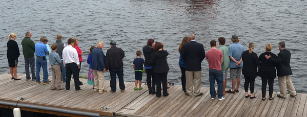 JIM VAIKNORAS/Staff photo The families of those lost at sea <br /> toss wreaths into the river during the Relocation Ceremony for the Newburyport Fisherman's Memorial on the boardwalk on the Newburyport Waterfront Monday morning.