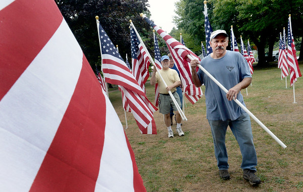 BRYAN EATON/Staff photo. Exchange Club of Greater Newburyport members Mick Viccaro, right, Ben Iacono and Jim Noyes, out of view, bring flags they assembled across the Field of Honor in Essex County Correctional inmates to install at the Bartlet Mall in Newburyport. A ceremony for the Field of Honor will take place on Sunday at noon with the arrival of veterans on motorcycles with a rembembrance of 911 which will have been 15 years ago.