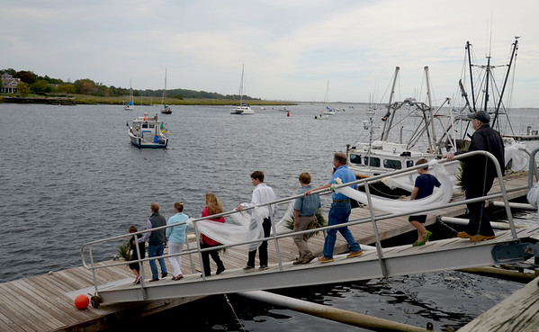 JIM VAIKNORAS/Staff photo The families of those lost at sea make their way down a ramp to toss wreaths into the river during the Relocation Ceremony for the Newburyport Fisherman's Memorial on the boardwalk on the Newburyport Waterfront Monday morning.