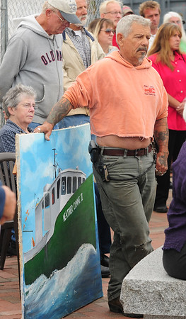 JIM VAIKNORAS/Staff photo Jay Vincent holds a painting of the Heather Lynne II, which once hung at Tri-Coastal Fishing Co-op, during the Relocation Ceremony for the Newburyport Fisherman's Memorial on the boardwalk on the Newburyport Waterfront Monday morning. The Heather Lynne II sank on September 5, 1996.