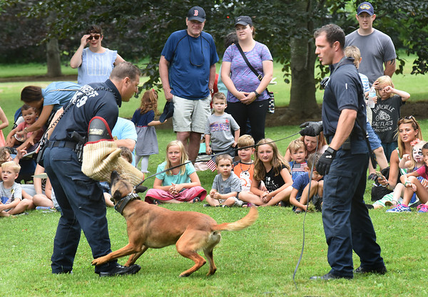 BRYAN EATON/Staff photo. Capt. Tom Cote, left, with Dash, and Sgt. Chris Auger of the Essex County Sheriff's Department K-9 Unit give a demonstation at Kids Day in the Park.