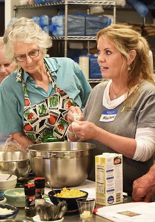 BRYAN EATON/Staff photo. Lehane, with Yvonne McQuilkin, rips up sourdought bread to put in her Corn Gazpacho.