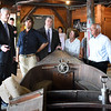 BRYAN EATON/Staff photo. Governor Charlie Baker, left, talks to Graham McKay of Lowell's Boat Shop in Amesbury during a tour of the place with Rep. Jim Kelcourse and Amesbury Mayor Ken Gray, right.