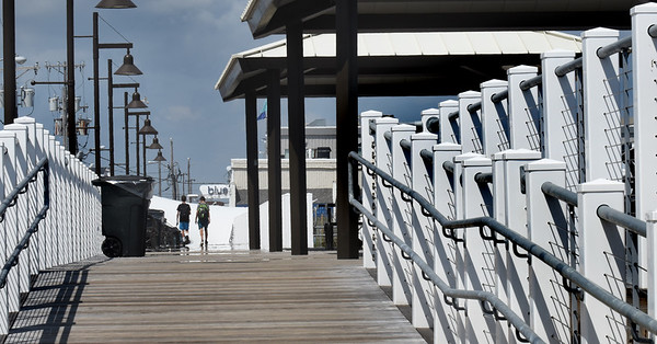 BRYAN EATON/Staff photo. Two beach-goers walk down the boardwalk at Salisbury Beach on Wednesday afternoon, the focal point  of many patterns.