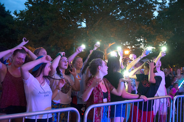 """JIM VAIKNORAS/Staff photo Fans wave their phones as they dance and sway to the Paul McCartney and Wing classic """"Maybe I'm Amazed"""" being performed by Beatlejuice at Market Landing Park in Newburyport Thursday night."""