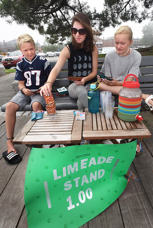 """BRYAN EATON/Staff photo. Juliet Moore, center, nanny to Christian Joyner, 9, and sister Aby, 12, all of Newbury sell limeade on Newburyport's boardwalk late Tuesday morning. WIth business a little slow they played the card game """"sleeping queen"""" with Christian winning most of them."""