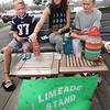 "BRYAN EATON/Staff photo. Juliet Moore, center, nanny to Christian Joyner, 9, and sister Aby, 12, all of Newbury sell limeade on Newburyport's boardwalk late Tuesday morning. WIth business a little slow they played the card game ""sleeping queen"" with Christian winning most of them."