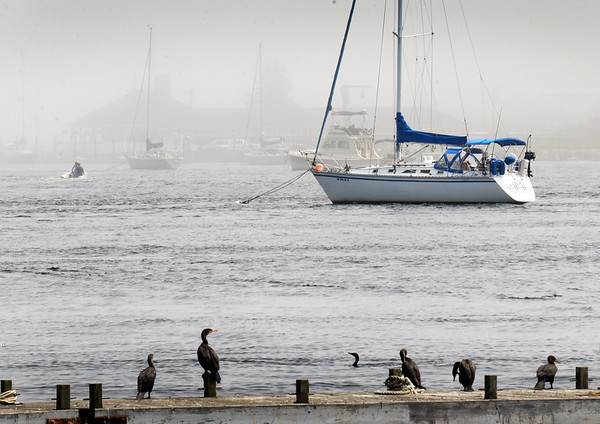 BRYAN EATON/Staff photo. Boaters head, upper left, head into the foggy Merrimack RIver in a view from Ring's Island pier in Salisbury on Tuesday afternoon. The humidity stays for awhile with the chance of precipitation possible into the weekend.