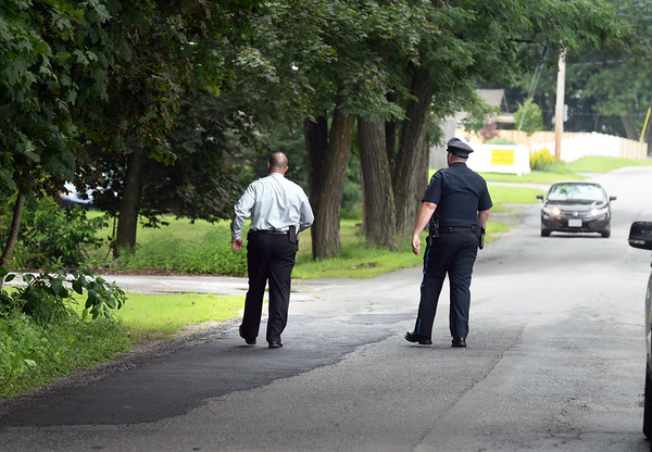 BRYAN EATON/Staff photo. Salisbury Police Detective Keith Forget, left, and another officer walk the area on High Street in Salisbury where a house was shot at late Sunday night looking to speak to neighbors.
