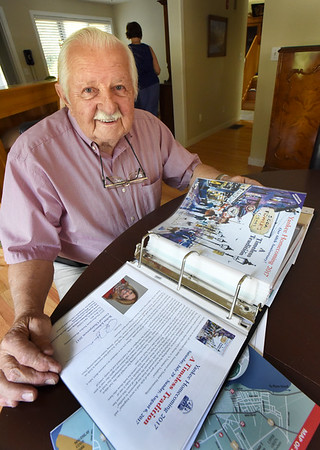 BRYAN EATON/Staff photo. Norman Jutras with his collection of Yankee Homecoming guidebooks. He was general chairman in 1975.