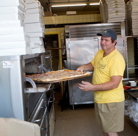 JIM VAIKNORAS/Staff photo Caesar Porreti removes a tray of hot pizza from the oven at Tripoli's at Salisbury Beach Center on a hot Wednesday afternoon.
