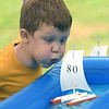 JIM VAIKNORAS/Staff photo Erik Repczynski, 6, uses his own wind to propel a boat  in rain gutter regatta at Family Day at Maudslay Saturday. He is with Scout Pack 21.