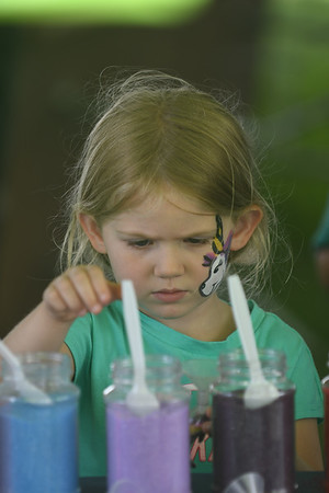 JIM VAIKNORAS/Staff photo Emily Plastridge, 4, picks out colors while making a sand art dolphin at Seabrook Old Home Days Sunday at Seabrook Elementary School.