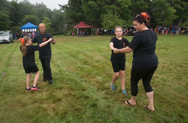 JIM VAIKNORAS/Staff photo Kaylah Graham dance with instructor Cris Plumley and Candace O'Brien dances with instructor Kristen Graham in the rain at Family Day at Maudslay Saturday. The quartet are from Footloose Dance Studio in Salisbury, and they were dancing the Cha-Cha.