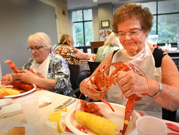 """BRYAN EATON/Staff photo. Maria Chouinard, left, and Lois Charte waste no time in the messy and delicious are of cracking open lobsters at the Amesbury Senior Center on Wednesday afternoon. They were at the very popular Lobster Dinner and Trivia Night with some """"name those tunes"""" thrown in as well."""