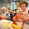 "BRYAN EATON/Staff photo. Maria Chouinard, left, and Lois Charte waste no time in the messy and delicious are of cracking open lobsters at the Amesbury Senior Center on Wednesday afternoon. They were at the very popular Lobster Dinner and Trivia Night with some ""name those tunes"" thrown in as well."