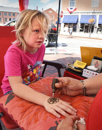 BRYAN EATON/Staff photo. Ally Hawkes, 7, gets her hand decorated by Maria O'Connor, Amesbury, who owns Ancient Fire Henna booth. Ally, a Newburyport native now living in Florida, was home visiting family.