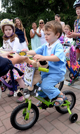 """BRYAN EATON/Staff photo. Austin Perry, 3, of Newton, N.H., whose family is from Newburyport, gets his prize for being the winner in the boys category of the Kids Day in the Park Carriage and Bicycle Parade with his """"Austin's Pet Clinic"""" get up."""
