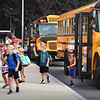 BRYAN EATON/Staff photo. Students jump out of the school buses as they return to the Bresnahan School in Newburyport on Tuesday. Amesbury students return to school today.