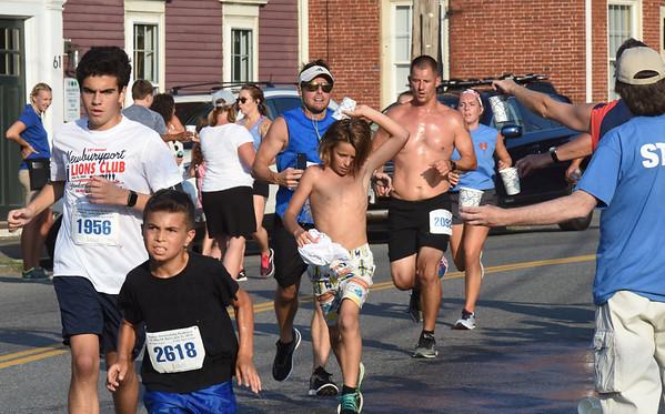 BRYAN EATON/Staff photo. Runners grab water on Water Street on the 5K race.