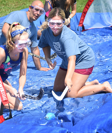 BRYAN EATON/Staff photo. Boys and Girls Club member Morgan Weaver, left, and counselor Kiley Keenan scramble for the ball in a game of soap hockey where water is sprayed on the tarp with the soap making for a slippery game yesterday morning. Afternoon activities were moved inside as the temperature hit the mid-90's.