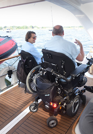 BRYAN EATON/Staff photo. Impossible Dream crew member David McCauley, left, chats with Amesbury resident Pete Govoni while heading out to sea.