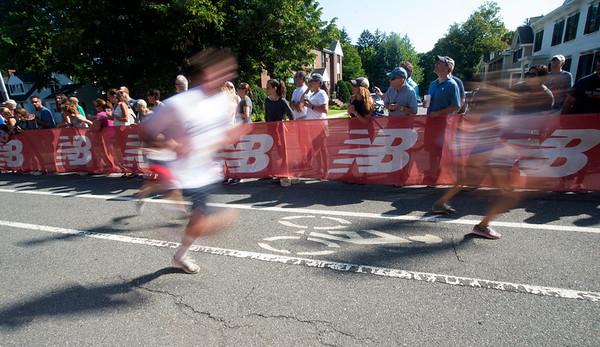 JIM VAIKNORAS/Staff photo Runners sprint past spectators at the High Street Mile Sunday morning in Newburyport.