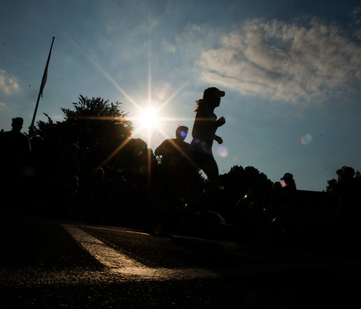JIM VAIKNORAS/Staff photo The sun sets behind runners at the Newburyport Lions Club Yankee Homecoming Road Race.