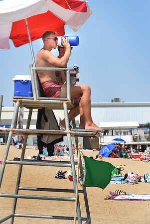 BRYAN EATON/Staff photo. Salisbury Beach lifeguard Jack Pettis of Haverhill sips from a cooler that he fills with ice in the morning and sips as it melts, as he and fellow guard Austin Hart of Andover keep watch over swimmers. There was a slight offshore breeze on Monday afternoon, not as cooling as an onshore one.