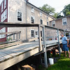 BRYAN EATON/Staff photo. Ken Turner, left, and Frank Goldberg lay lines as they put up decorative lighting at Lowell's Boat Shop for their pig roast fundraiser next weekend.