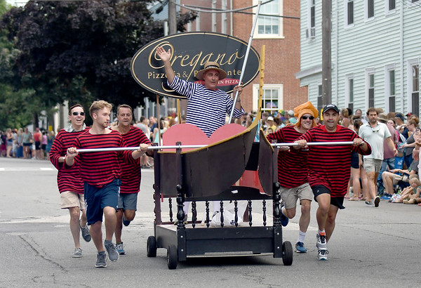 JIM VAIKNORAS/Staff photo The crew from Oregano puch a gondola bed at the Lions Club Bed Race on Federal Street in Newburyport Thursday night.