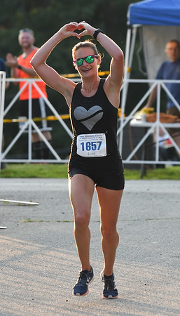JIM VAIKNORAS/Staff photo  Amanda Nurse makes a heart with her hands as she is the female winner of the 10 mile  in the Newburyport Lions Club Yankee Homecoming Road Race.