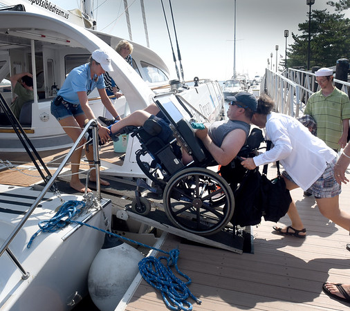 BRYAN EATON/Staff photo. First mate Paulina Belsky helps Opportunity Works client Donny Duggan aboard on a special ramp.