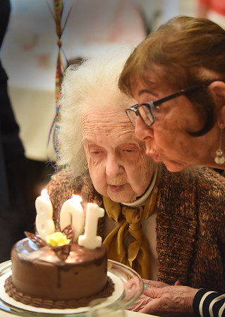 BRYAN EATON/Staff photo. Christel Rogers of Beverly helps Clara Sillars blow the candles of her birthday cake as she turned 108 years old. They have been friends for 45 years and worked together at Johnny Appleseed.