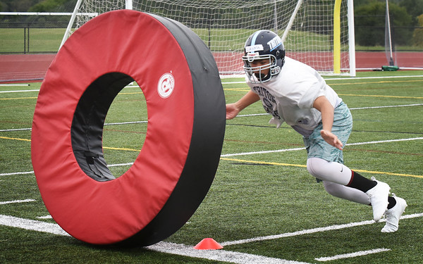 BRYAN EATON/Staff photo. Triton High School football players practice tackling skills on a huge rolling donut.