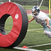 BRYAN EATON/Staff photo. Triton High School football players practice tackling skills on a huge rolling donut.